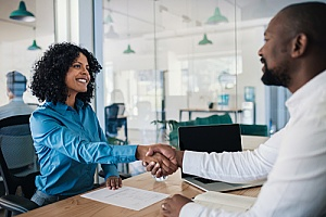 a small business owner shaking hands with a third-party HR consultant