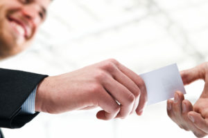 HR consultant hands business card to a prospective client