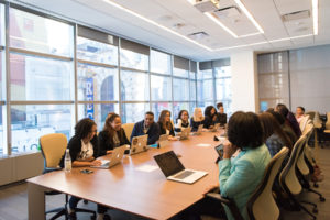 HR consulting firm and their client amployees convene into a room for a meeting