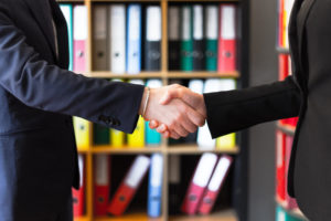 a HR consulting firm employee and an executive of a prospective client shake hands