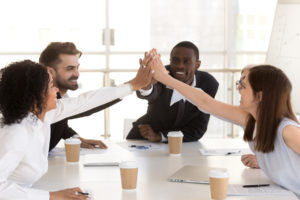 co-workers high-five each other after vowing to stop microaggressions