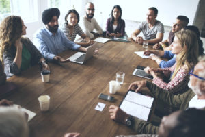 employees surround the table to learn how workplace discipline will be enforced
