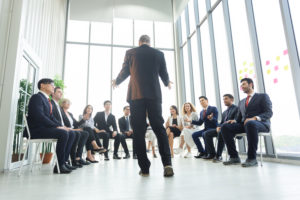 executive tells the employees sitting down the new hr compliance laws