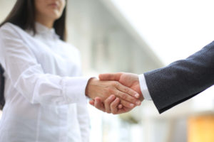 hr consultant shakes employee hand before they talk about the conflict in the workplace