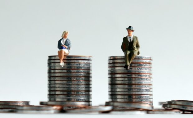 Why Equal Pay Matters In The Workplace-Man and Women Dummy Sitting on Equals Coins