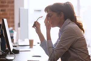 a gaslit employee who is sitting at her desk frustrated
