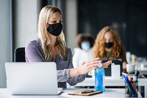 woman with face mask back at work in office after lockdown