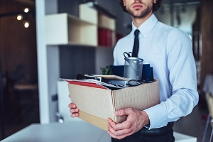businessman in light modern office with carton box