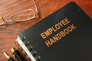 employee handbook on a wooden table and glasses