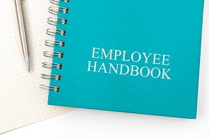employee handbook or manual with a pen and paper on a white table in an office