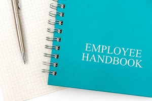employee handbook or manual with a pen