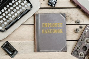 employee handbook text on cover of old book on office desk