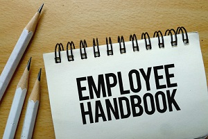 employee handbook text written on a notebook with pencils