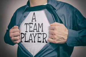 man showing a team player tittle on t-shirt