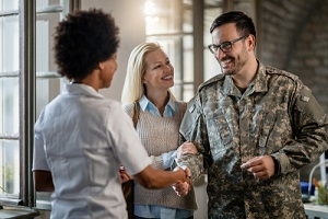 military man shaking hands with female doctor while being with his wife at medical counselling