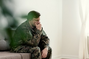 sad soldier in uniform covering his mouth while sitting on a sofa
